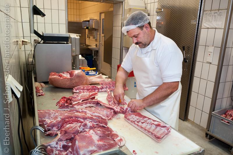 Metzger beim Zerlegen einer Schweinehälfte